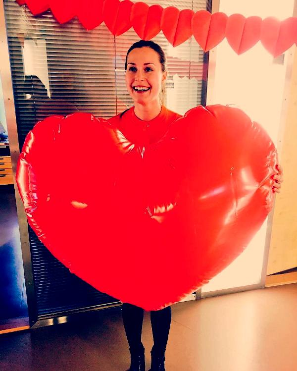 Sanna Marin posing with a big heart on Valentines Day in the Parliament of Finland