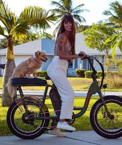 Emily Zeck riding a bike with her pet dog