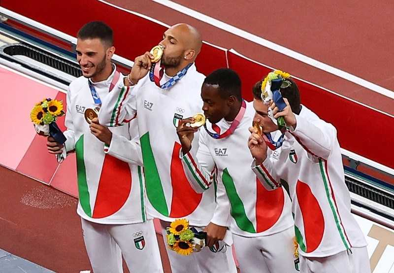 Lamont Marcell Jacobs, along with the Italian team for 4×100 m relay event, kissing his gold medal he won at the 2020 Tokyo Olympics
